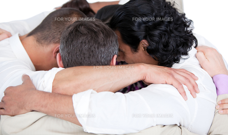 Confident business team hugging each other in a circleの写真素材 [FYI00482308]