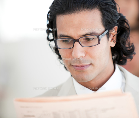 Confident businessman reading a newspaperの素材 [FYI00482310]
