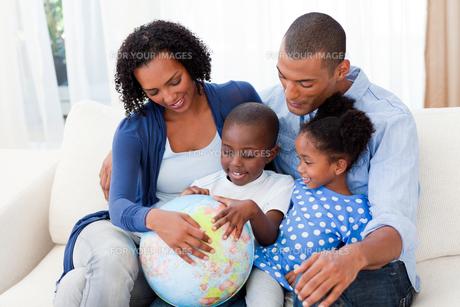 Happy family holding a terrestrial globeの写真素材 [FYI00482320]
