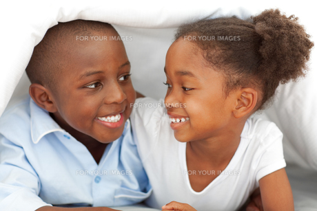 Portrait of laughing siblings lying down on bedの写真素材 [FYI00482322]