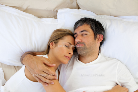 Caring lovers sleeping lying in the bedの写真素材 [FYI00482328]