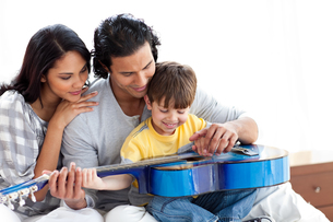 Happy little boy playing guitar with his parentsの写真素材 [FYI00482333]