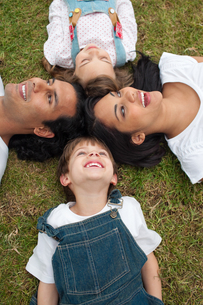 Cute children and their parents lying on the grassの写真素材 [FYI00482343]