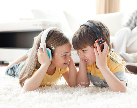 Siblings playing on the floor with headphonesの写真素材 [FYI00482345]