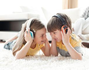 Siblings playing on the floor with headphonesの素材 [FYI00482345]