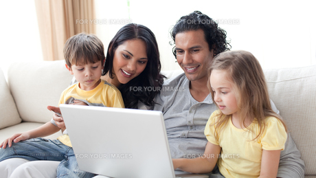 Affectionate parents using laptop with their childrenの写真素材 [FYI00482347]