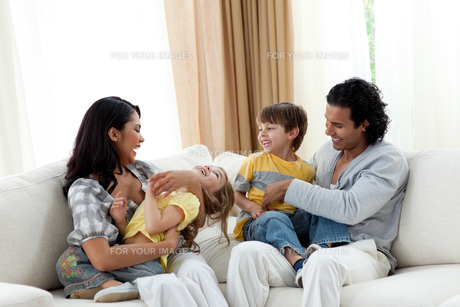 Earing parents playing with their children on sofaの写真素材 [FYI00482349]