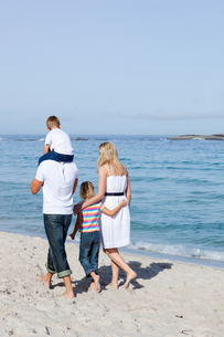 Cheerful family walking on the sandの写真素材 [FYI00482355]