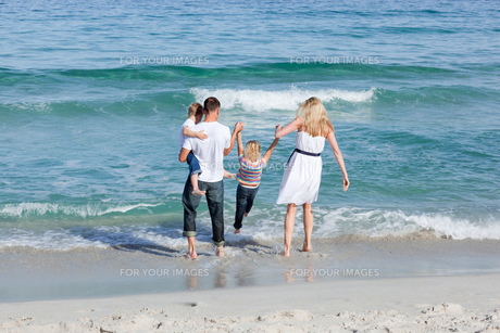Jolly family walking on the sandの写真素材 [FYI00482356]