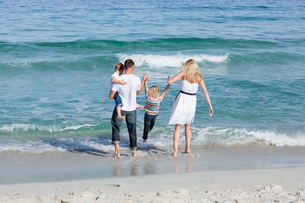 Jolly family walking on the sandの素材 [FYI00482356]