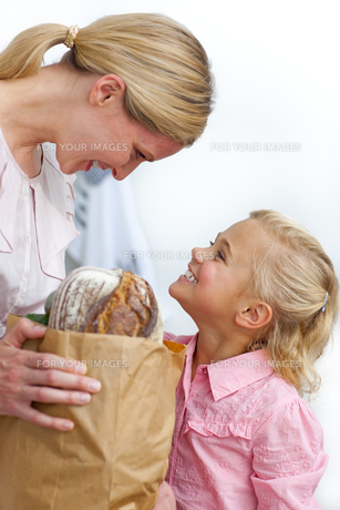 Smiling mother and her daughter unpacking grocery bagの素材 [FYI00482363]