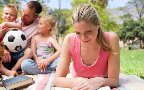 Concentrated mother reading at a picnic with her familyの写真素材 [FYI00482369]