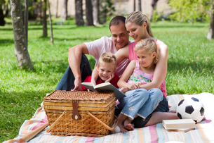 Happy family reading in a parkの写真素材 [FYI00482370]