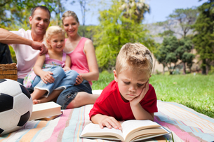 Concentrated blond boy reading while having a picnic with his familyの写真素材 [FYI00482372]