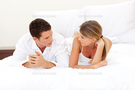 Young couple discussing lying on their bedの素材 [FYI00482373]