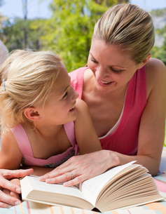 Portrait of a smiling mother and her daughter reading at a picnicの写真素材 [FYI00482375]