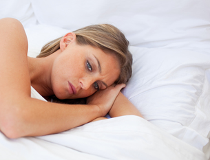 Worried woman lying on her bedの写真素材 [FYI00482377]