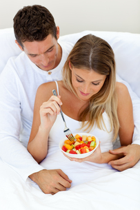 Intimate couple eating fruit lying on their bedの写真素材 [FYI00482379]