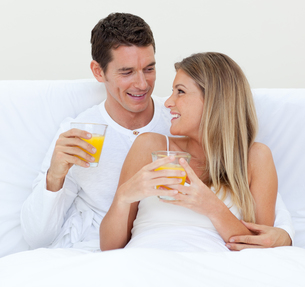 Intimate couple drinking orange juice lying on their bedの写真素材 [FYI00482380]
