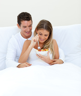 Affectionate couple eating fruit lying on their bedの写真素材 [FYI00482381]