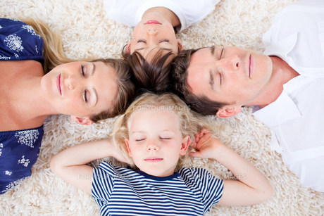 Relaxed family lying in circle on the wallto-wall carpetの写真素材 [FYI00482384]