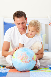 Attentive father and his daughter looking at a terretrial globeの写真素材 [FYI00482396]