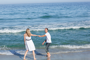 Affectionate couple walking at the seasideの写真素材 [FYI00482397]