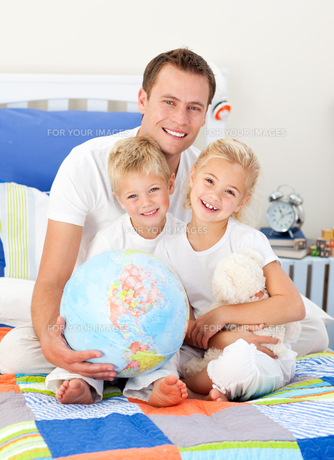 Cheerful father and his children holding a terretrial globeの写真素材 [FYI00482399]
