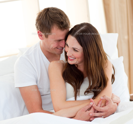 Romantic lovers embracing lying in bedの写真素材 [FYI00482409]