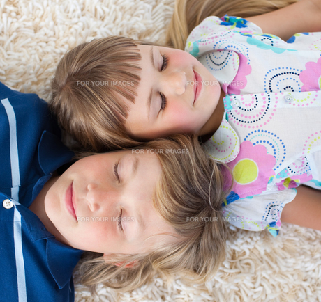 Siblings sleeping on the floorの写真素材 [FYI00482414]