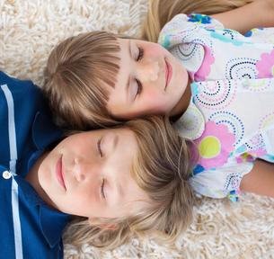 Siblings sleeping on the floorの写真素材 [FYI00482414]