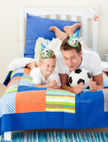 Adorable child and his father playing with a soccer ballの写真素材 [FYI00482416]