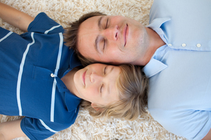 Father and his son lying on the floorの写真素材 [FYI00482419]