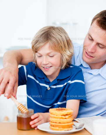 Adorable boy and his father putting honey on wafflesの写真素材 [FYI00482420]