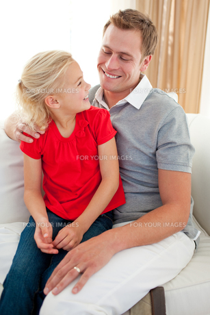 Adorable little girl sitting on sofa with her fatherの素材 [FYI00482421]