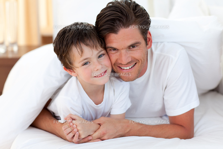 Smiling father and his son lying on bedの写真素材 [FYI00482423]