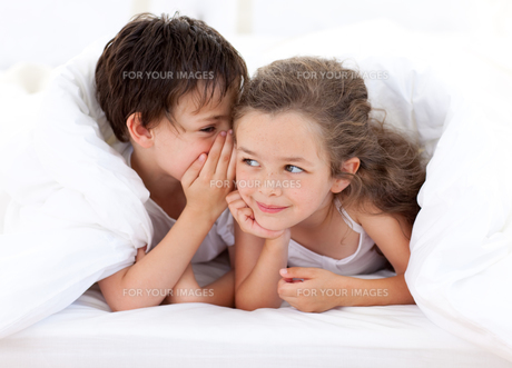 Siblings playing on parents bedの写真素材 [FYI00482426]