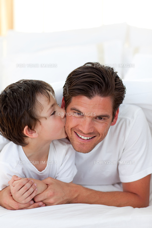 Little boy kissing his father lying on bedの写真素材 [FYI00482427]
