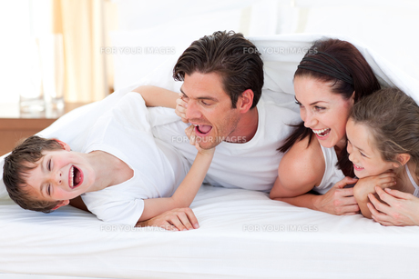Happy family having fun lying on bedの写真素材 [FYI00482430]