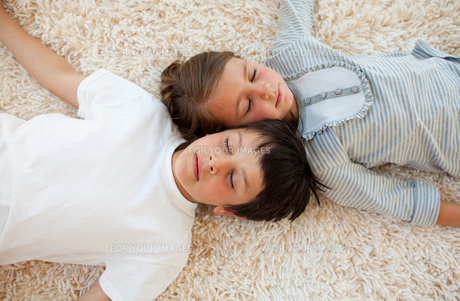 Siblings sleeping on the floorの写真素材 [FYI00482438]