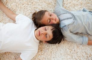 Siblings sleeping on the floorの写真素材 [FYI00482438]