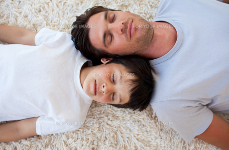 Father and his son sleeping on the floorの写真素材 [FYI00482439]