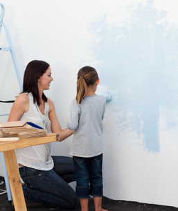 Mother and her daughter painting a wall togetherの写真素材 [FYI00482441]