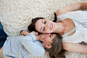 Smiling mother and her daughter lying on the floorの素材 [FYI00482445]