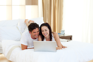 Happy couple using a laptop lying on their bedの写真素材 [FYI00482450]