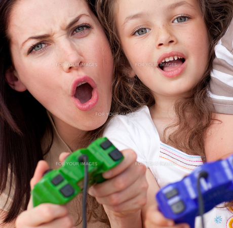 Excited mother and her daughter playing video gamesの写真素材 [FYI00482454]