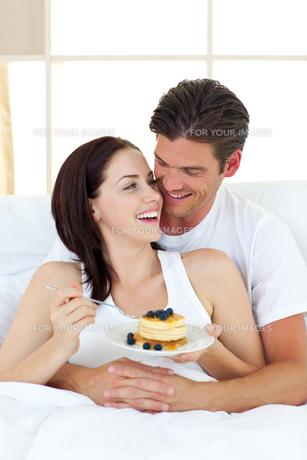 Joyful couple eating pancakes lying on their bedの写真素材 [FYI00482455]