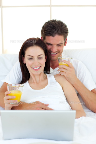 Lovers using a laptop on their bedの写真素材 [FYI00482456]