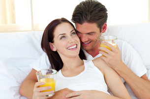 Young couple drinking orange juice lying on their bedの写真素材 [FYI00482457]