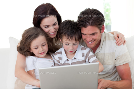 Family using a laptop on the sofaの写真素材 [FYI00482460]